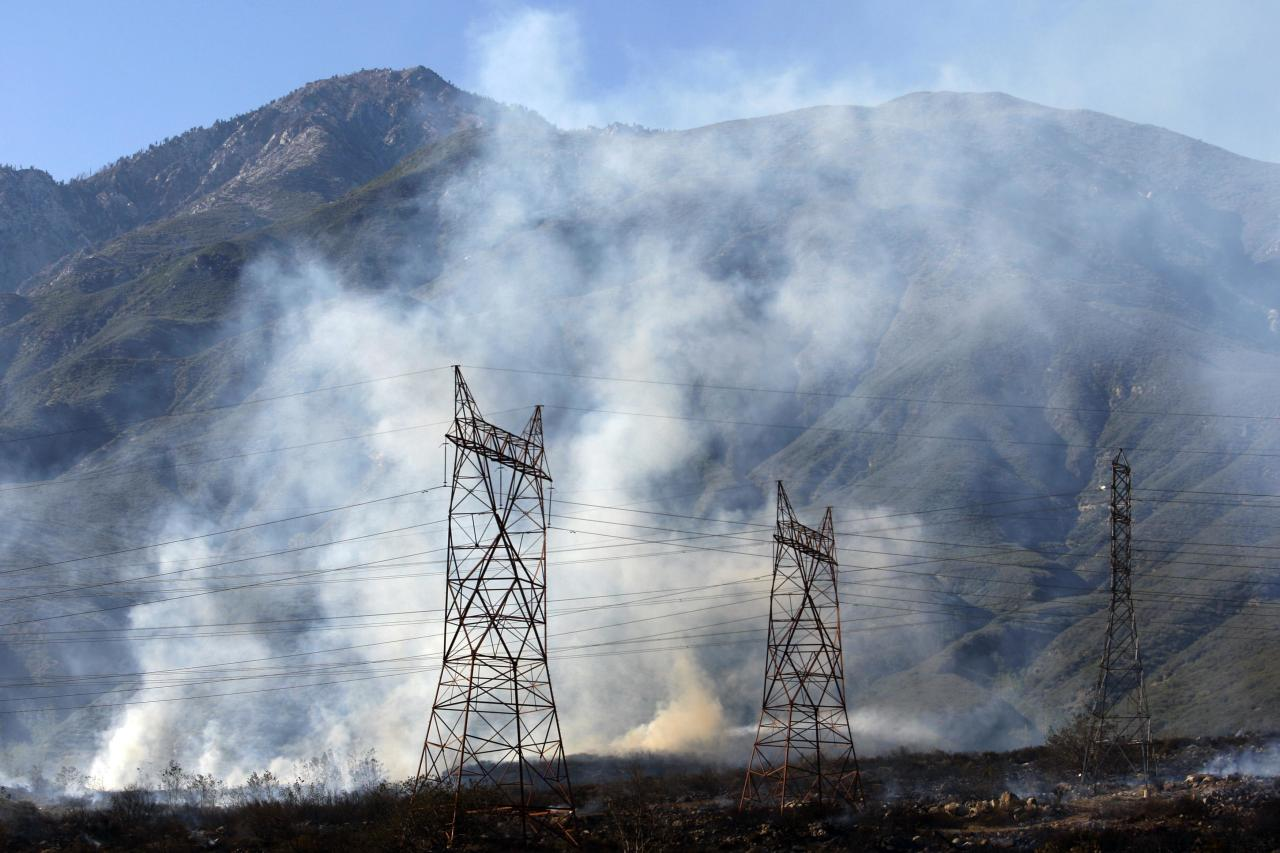 Smoke rises near power lines with Cucamonga Peak in the distance at a wildfire in Rancho Cucamonga, California, April 30, 2014. The wind-driven brush fire burning out of control in the drought-parched Southern California wildland on Wednesday threatened a wealthy community in the foothills of the San Bernardino Mountains and forced the evacuation of hundreds of residents, officials said. REUTERS/David McNew (UNITED STATES - Tags: DISASTER)