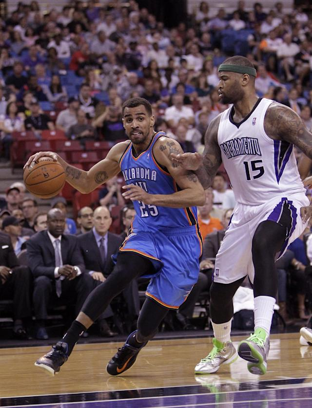 Oklahoma City Thunder guard Thabo Sefolosha, of Switzerland, drives against Sacramento Kings center DeMarcus Cousins during the first quarter of an NBA basketball game, Tuesday, April 8, 2014, in Sacramento, Calif. (AP Photo/Rich Pedroncelli)