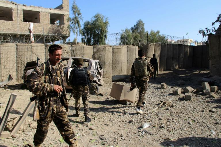 Afghan security personnel inspect the site of a car bomb attack in Lashkar Gah which killed at least two soldiers