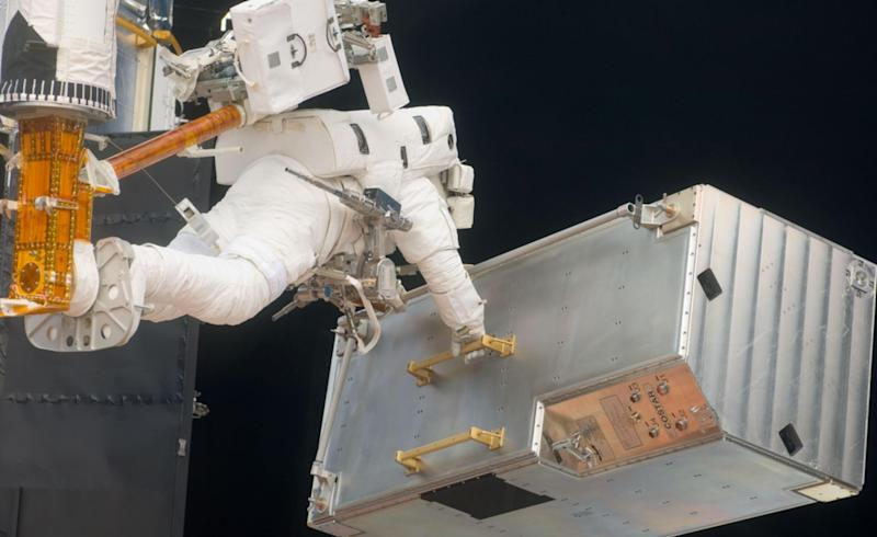 STS-125 Mission Specialist Andrew Feustel positioned on a foot restraint on the end of Atlantis' remote manipulator system moves the Corrective Optics Space Telescope Axial Replacement (COSTAR) during the mission's third session of extravehicular activity (EVA) as work continues to refurbish and upgrade the Hubble Space Telescope. Photo credit: NASA May 16, 2009