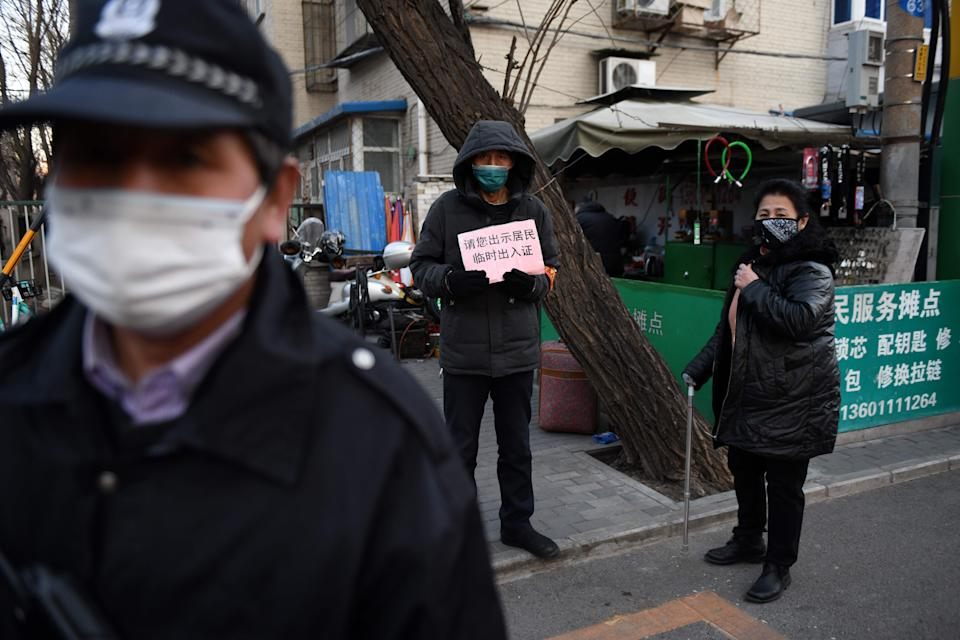 """A volunteer holds a sign which reads """"Please show your temporary entrance card"""" as he stands with a security guard at the entrance of a residential compound in Beijing on March 4, 2020. - Most residential compounds in Beijing are refusing entry to visitors and only allowing registered residents to enter, as a precaution against the spread of the COVID-19 coronavirus. China on March 4 reported 38 more deaths from the new coronavirus but a fall in fresh cases for a third consecutive day. (Photo by GREG BAKER / AFP) (Photo by GREG BAKER/AFP via Getty Images)"""