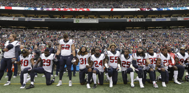 Houston Texans players kneel and stand during the singing of the national anthem Sunday. (AP Photo/Elaine Thompson)