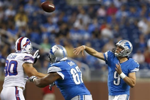 Detroit Lions quarterback Matthew Stafford (9) passes the ball as guard Rob Sims (67) blocks Buffalo Bills defensive end Chris Kelsay (90) during the first quarter of an NFL preseason football game in Detroit, Thursday, Aug. 30, 2012. (AP Photo/Rick Osentoski)