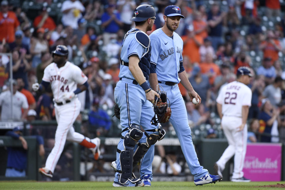 Toronto Blue Jays starting pitcher Steven Matz, right, and catcher Danny Jansen walk to the mound as Houston Astros' Yordan Alvarez, back left, runs the bases after hitting a two-run home run during the fourth inning of a baseball game Saturday, May 8, 2021, in Houston. (AP Photo/Eric Christian Smith)
