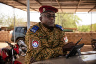 """Salomon Tibiri, a pastor and military chaplain, checks his phone at the 10th RCAS barracks in Kaya, Burkina Faso, Saturday, April 10, 2021. Tibiri has been offering soldiers spiritual succor for more than 15 years. But he's never fielded as many calls from anxious soldiers as in recent years, when the army found itself under attack by Islamic extremist fighters. """"Now (the soldiers) are busier, and when you approach them you feel their stress — much more stress,"""" he says. (AP Photo/Sophie Garcia)"""