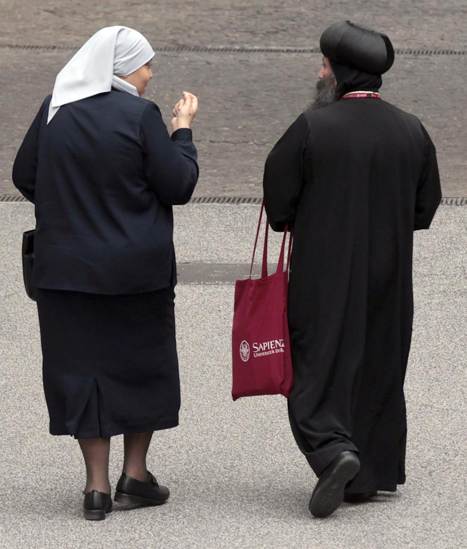 A nun and a Coptic priest share a word outside the Augustinianum institute where an international congress on Coptic studies is held in Rome, Wednesday, Sept. 19, 2012. Scholars are questioning the authenticity and significance of a much-publicized discovery by a Harvard scholar who reported that a 4th Century fragment of papyrus has provided the first evidence that some early Christians believed Jesus was married. Karen King, a professor at Harvard Divinity School, announced the finding Tuesday at an international congress on Coptic studies in Rome. (AP Photo/Gregorio Borgia)