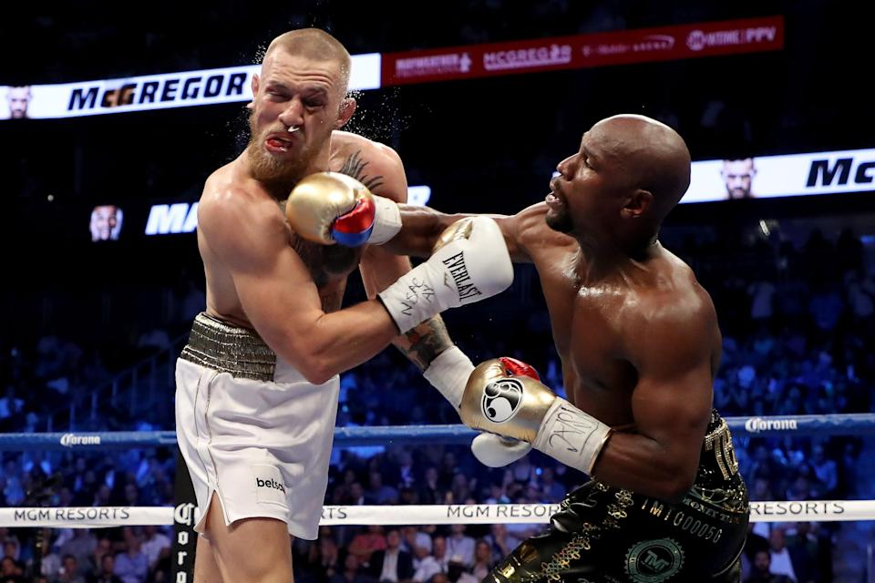 Floyd Mayweather Jr. throws a punch at Conor McGregor during their super welterweight boxing match on Aug. 26, 2017, at T-Mobile Arena in Las Vegas. (Getty Images)