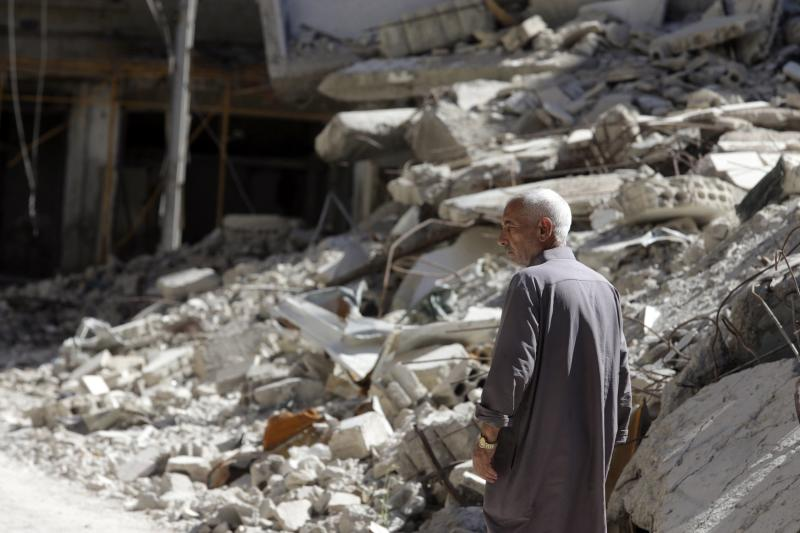 Man walks by damage and debris in Ain Tarma, in the eastern Ghouta suburb of Damascus