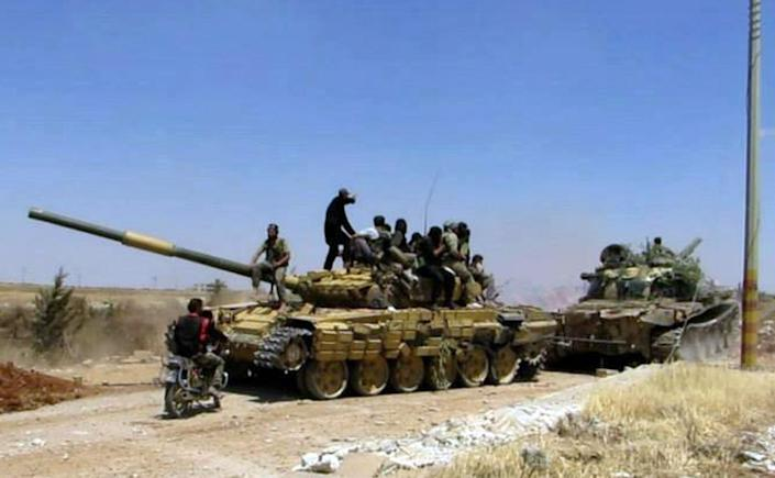 In this Friday, June 14, 2013 citizen journalism image provided by Edlib News Network, ENN, Syrian rebels gather on top of a tank they took after storming the Iskan military base in Idlib province, northern Syria. After weeks of fighting the rebels captured tanks as well as other vehicles and artillery in the area. (AP Photo/Edlib News Network ENN) THE ASSOCIATED PRESS IS UNABLE TO INDEPENDENTLY VERIFY THE AUTHENTICITY, CONTENT, LOCATION OR DATE OF THIS HANDOUT PHOTO.