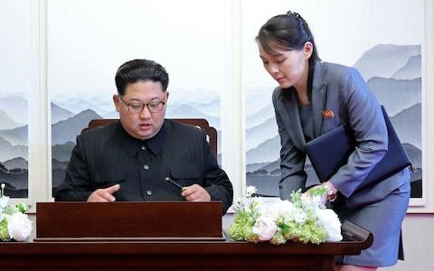 North Korean leader Kim Jong Un, left, signs a guest book next to his sister Kim Yo Jong - Credit: AP