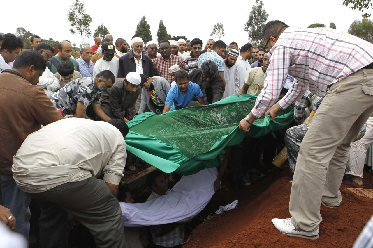 ATTENTION EDITORS - VISUAL COVERAGE OF SCENES OF INJURY OR DEATH   Relatives and Muslim faithful bury the slain body of Rehmad Mehbub, 18, who was killed in a crossfire between armed men and the police at the Westgate shopping mall, in Kenya's capital Nairobi September 22, 2013. Islamist militants were holed up with hostages on Sunday at a shopping mall in Nairobi, where at least 59 people have been killed in an attack by the al Shabaab group that opposes Kenya's participation in a peacekeeping mission in neighbouring Somalia. REUTERS/Thomas Mukoya (KENYA - Tags: CIVIL UNREST CRIME LAW OBITUARY)   TEMPLATE OUT