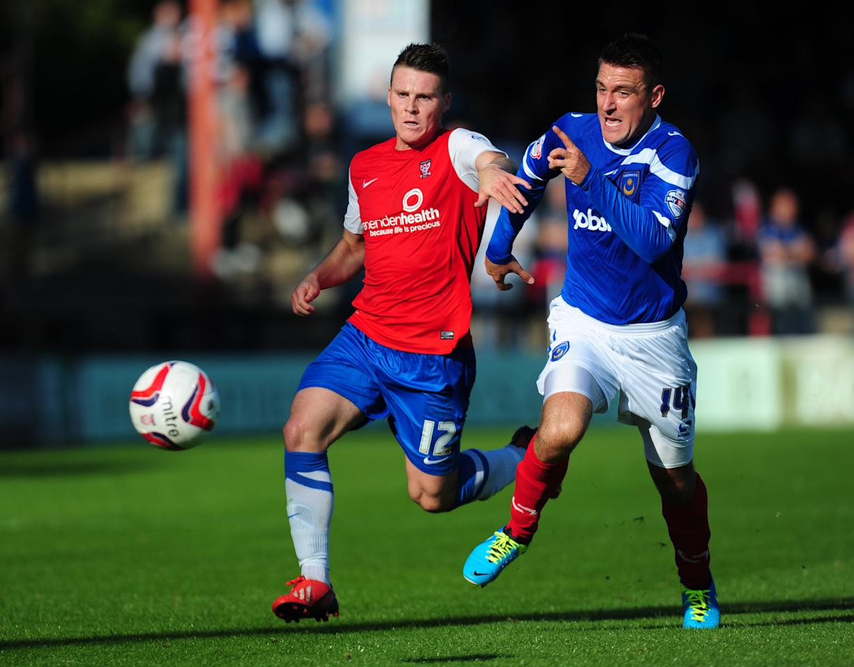 York City's Josh Carson (left) and Portsmouth's Marcos Painter in action during the Sky Bet League Two match at Bootham Crescent, York.