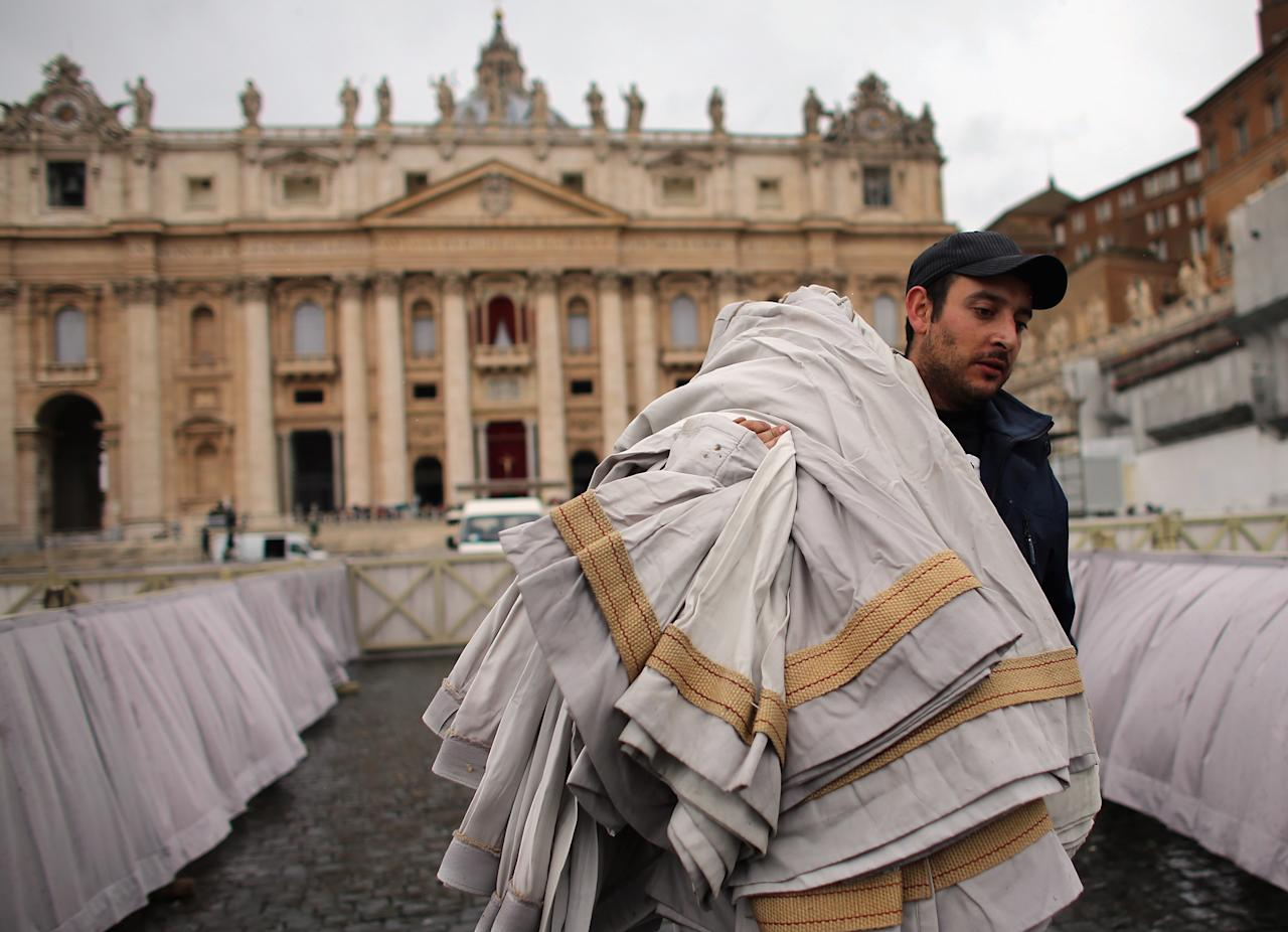 VATICAN CITY, VATICAN- MARCH 18:  A worker carries bunting as he helps prepare Saint Peter Square for the inauguration mass on March 18, 2013 in Vatican City, Vatican. The Inauguration Mass for Pope Francis will take place on March 19, the feast day for St. Joseph. (Photo by Joe Raedle/Getty Images)