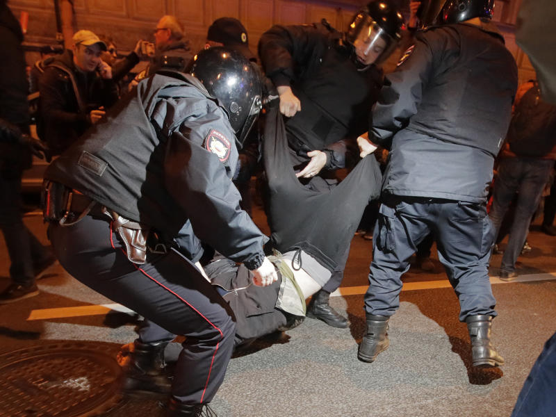 Riot police officers detain a protester during a rally in St.Petersburg: AP