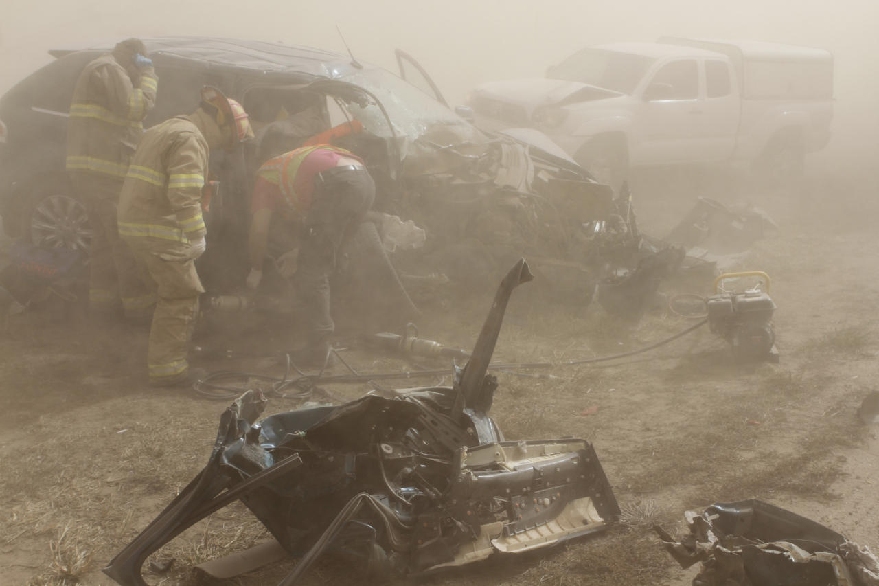 Rescue personnel from the Tonkawa Fire Department extricate a woman pinned in vehicle after it was involved in an accident on Interstate 35, one of 12 accidents involving 27 vehicles which took place during massive dust storms sweeping through Kay County, Okla. on October 18, 2012. Ambulances from the cities of Blackwell, Tonkawa and Ponca City transported injured drivers and passengers to hospitals in Blackwell and Ponca City.  (AP Photo/The Ponca City News, Rolf Clements)