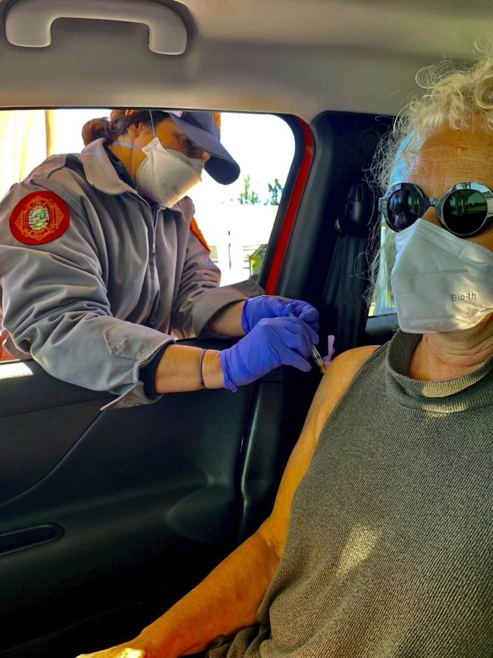 This undated photo provided by Tami Katz–Freiman, of Miami, shows her getting a COVID-19 vaccine. Katz-Freiman, 65, got her second dose, and plans to watch the Miami Film Festival virtually Sunday, March 7, 2021, at the home of unvaccinated friends. All will wear masks. The Biden administration said Friday, March 5, it's focused on getting the guidance for those fully vaccinated right and accommodating emerging science. (Tami Katz–Freiman via AP)