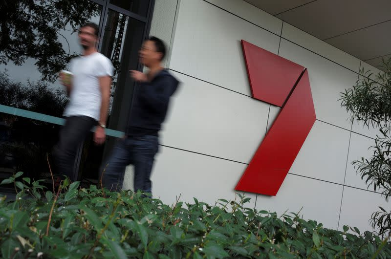 FILE PHOTO: Workers walk past the headquarters of media broadcaster/publisher Seven West Media in Sydney