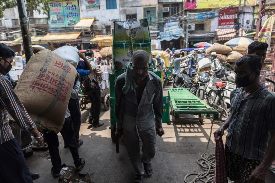 A worker pulls a loaded cart into an alley in Fatehpuri Market after the government eased a nationwide lockdown imposed as a preventive measure against the COVID-19 coronavirus in New Delhi on June 12, 2020. (Photo by XAVIER GALIANA / AFP) (Photo by XAVIER GALIANA/AFP via Getty Images)