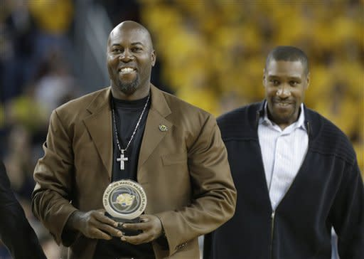 Glen Rice, left, walks with former teammate Mark Hughes during the first half of an NCAA college basketball game between Michigan and Penn State at Crisler Center in Ann Arbor, Mich., Sunday, Feb. 17, 2013. Rice received an award as a Top 75 All-Time March Madness Player. (AP Photo/Carlos Osorio)