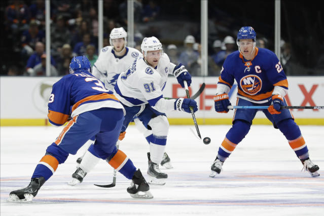 Tampa Bay Lightning's Steven Stamkos (91) passes the puck away from New York Islanders' Adam Pelech (3) and Anders Lee (27) during the first period of an NHL hockey game Friday, Nov. 1, 2019, in Uniondale, N.Y. (AP Photo/Frank Franklin II)