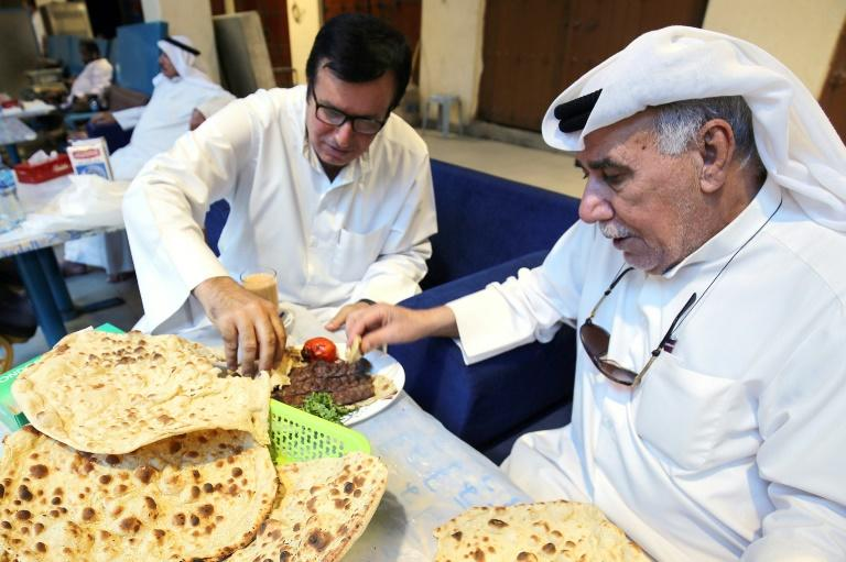 Hassan Abdullah Zachriaa (R), a Kuwaiti of Iranian origin and owner of the Al-Walimah restaurant, shares Iranian bread - known as taftoon - during a meal with a friend. The bread has been a staple of Kuwaiti meals for decades