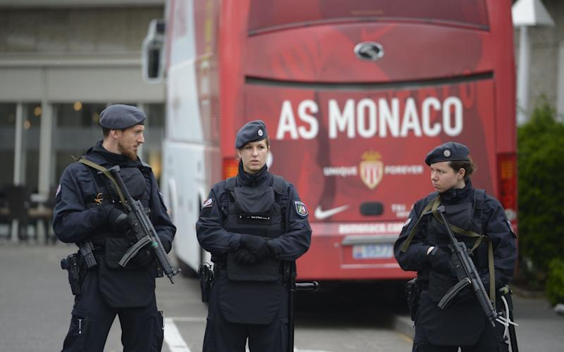 Policemen stand guard in front of a team bus of French football club AS Monaco - Credit: SASCHA SCHUERMANN/AFP