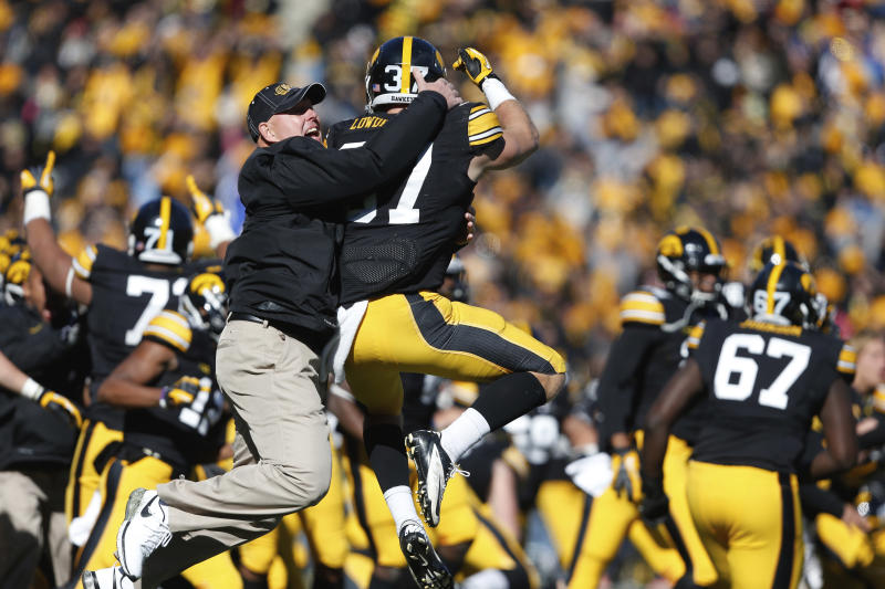 """FILE - In this Oct. 26, 2013, file photo, Iowa strength and conditioning coach Chris Doyle, front left, celebrates with defensive back John Lowdermilk (37) following their win in overtime against Northwestern in an NCAA college football game  in Iowa City, Iowa. Iowa football strength and conditioning coach Doyle has been placed on administrative leave after several black former players posted on social media about what they described as systemic racism in the program. Head coach Kirk Ferentz made the announcement Saturday, June 6, 2020, calling it """"a defining moment"""" for Iowa's football program in a video posted on the team's Twitter account. (AP Photo/Brian Ray, File )"""