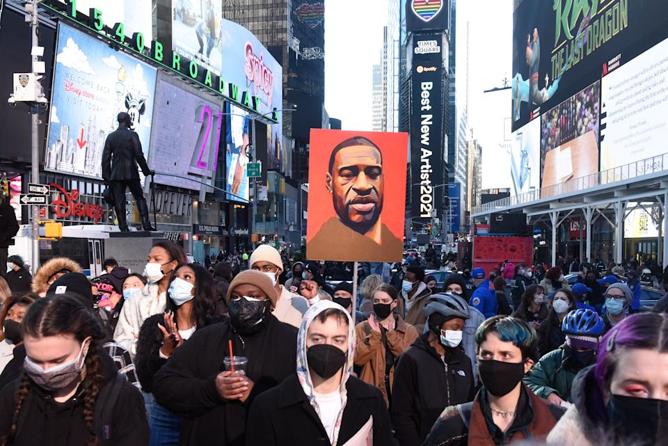 A person holds a placard with George Floyd's face during a protest to mark the one year anniversary of Breonna Taylor's death on March 13, 2021 in New York City. (Photo by Stephanie Keith/Getty Images)