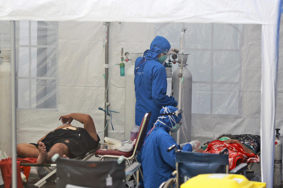 Medical workers treat patients inside an emergency tent erected to accommodate a surge in COVID-19 cases, at Dr. Sardjito Central Hospital in Yogyakarta, Indonesia, Sunday, July 4, 2021. A number of COVID-19 patients died amid an oxygen shortage at the hospital on the main island of Java following a nationwide surge of coronavirus infections. (AP Photo/Kalandra)