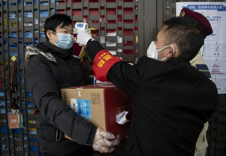 A security guard checks a man's temperature at the entrance to an apartment building in Hangzhou