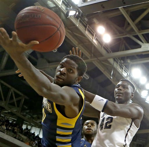 Marquette's Jamil Wilson, left, reaches oout trying to keep the ball from going out-of-bounds in front of Pittsburgh's Talib Zanna (42) during the first half of an NCAA college basketball game, Saturday, Jan. 12, 2013, in Pittsburgh. (AP Photo/Keith Srakocic)