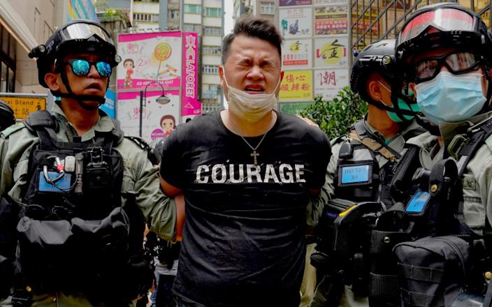 Police detain a protester after spraying pepper spray during a protest in Causeway Bay before the annual handover march in Hong Kong, - AP