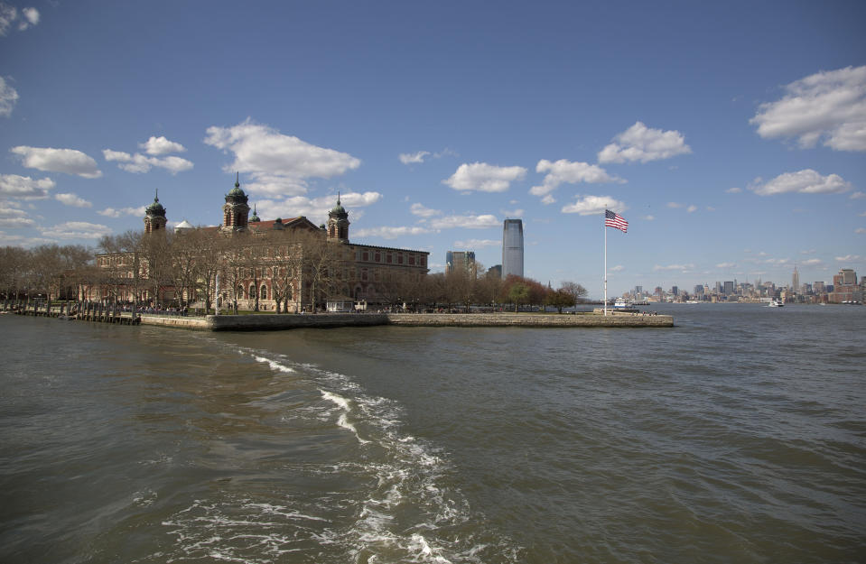 FILE - The wake from a ferry is seen trailing the boat as it leaves Ellis Island for Manhattan, on April 29, 2015, in New York. The location is featured in a collection of mini-essays by American writers published online by the Frommer's guidebook company about places they believe helped shape and define America. (AP Photo/Julie Jacobson, File)