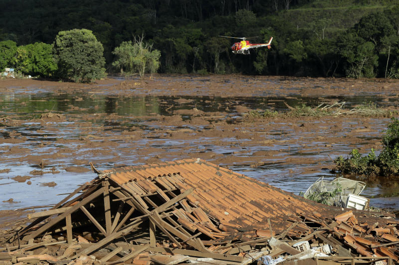 Rescue workers in a helicopter search a flooded area after a dam collapsed in Brumadinho, Brazil, Sunday, Jan. 27, 2019. A massive, deadly river of pale brown mud released by the collapse of a mining company dam on Friday threatens to cause an environmental disaster for Brazil, potentially snatching away livelihoods and driving the spread of disease, activists warned Sunday. (AP Photo/Andre Penner)