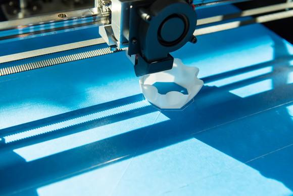 Close-up of a 3D printer printing a small, white plastic object on a blue surface.