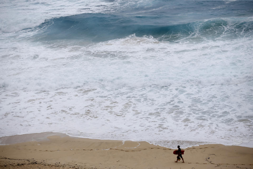 <p>A boogie boarder walks near the surf at Makapu'u Beach, Friday, Aug. 24, 2018, in Waimanalo, Hawaii. As Hurricane Lane approaches Oahu, large ocean swells have impacted the coastline. (Photo: Marco Garcia/AP) </p>