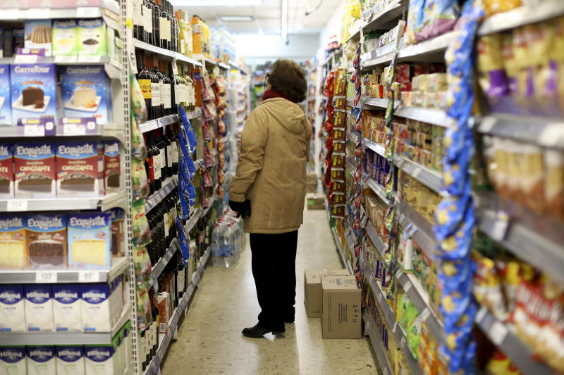 """A woman checks prices at a supermarket in Buenos Aires, Argentina, Wednesday, Aug. 14, 2019. President Mauricio Macri announced economic relief for poor and working-class Argentines that include an increased minimum wage, reduced payroll taxes, a bonus for informal workers and a freeze in gasoline prices. The conservative leader said Wednesday he's acting in recognition of the """"anger"""" Argentines expressed in Sunday's primary election, when Macri trailed his populist rival by 15 percentage points. (AP Photo/Natacha Pisarenko)"""