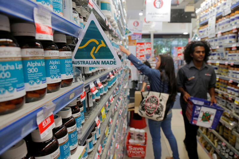 A shopper (L) browses for health products in an aisle stocked with vitamin supplements at a Mr Vitamins store in Sydney