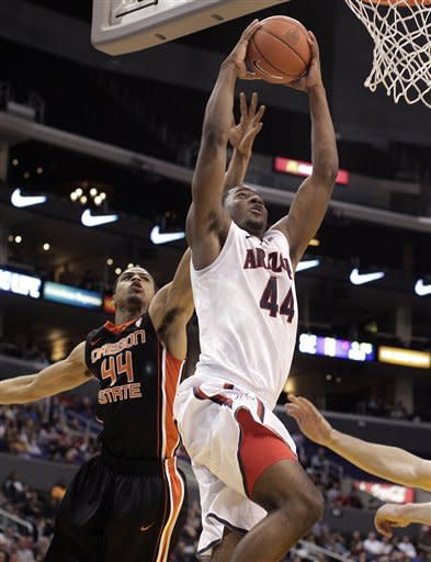 Arizona's Solomon Hill, center, goes up for a basket as he is defended by Oregon State's Devon Collier during the first half of an NCAA college basketball game in the semifinals of the Pac-12 Conference championship in Los Angeles, Friday, March 9, 2012. (AP Photo/Jae C. Hong)