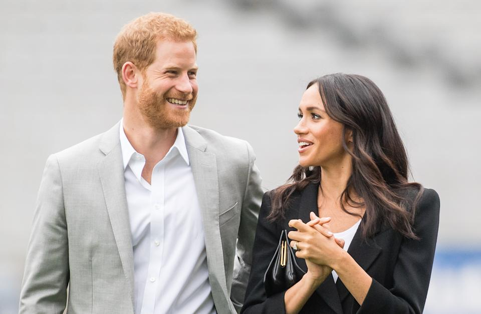 Prince Harry laughs as Meghan Markle looks at him wearing a black blazer