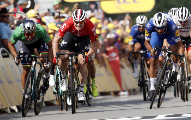Colombia's Fernando Gaviria, right, crosses the finish line to win the fourth stage of the Tour de France cycling race over 195 kilometers (121 miles) with start in La Baule and finish in Sarzeau, France, Tuesday, July 10, 2018. Slovakia's Peter Sagan, left, finished second and Germany's Andre Greipel, center, third. (AP Photo/Christophe Ena )