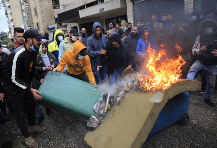 Protesters set fire to garbage containers in front the house of a Lebanese lawmaker, during a protest against deteriorating living conditions and strict coronavirus lockdown measures, in Tripoli, north Lebanon, Thursday, Jan. 28, 2021. Violent confrontations overnight between protesters and security forces in northern Lebanon left a 30-year-old man dead and more than 220 people injured, the state news agency said Thursday. (AP Photo/Hussein Malla)
