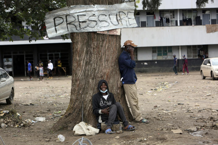 A man smiles while sitting under a tree in Harare, Zimbabwe, Thursday, Sept, 16, 2021. Zimbabwe has told all government employees to get vaccinated against COVID-19 or they will not be allowed to come to work. It wasn't made clear what would happen to those who refused to be vaccinated. (AP Photo/Tsvnagirayi Mukwazhi)