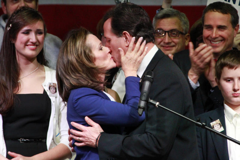 Republican presidential candidate, former Pennsylvania Sen. Rick Santorum, center right, kisses his wife Karen before speaking to supporters at an election night party at Steubenville High School in Steubenville, Ohio, Tuesday, March 6, 2012. (AP Photo/Gene J. Puskar)