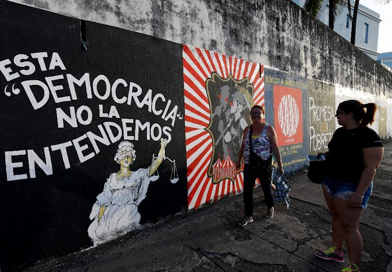 People walk past murals protesting the state of the economy in San Juan, Puerto Rico, as the former Spanish colony of 3.5 million, now a US territory, struggles under a mountain of debt