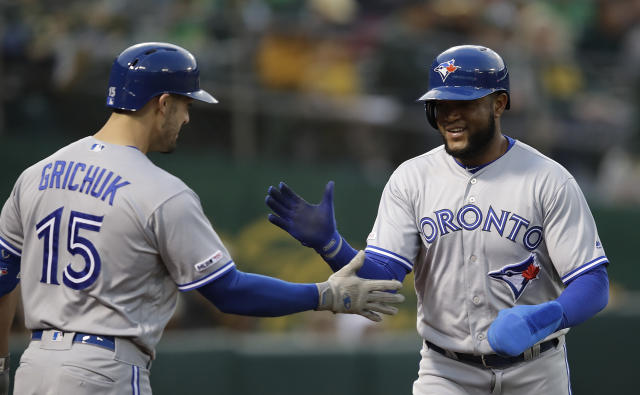 Toronto Blue Jays' Socrates Brito, right, is congratulated by Randal Grichuk (15) after scoring against the Oakland Athletics in the second inning of a baseball game Friday, April 19, 2019, in Oakland, Calif. Brito scored on a double by Toronto's Eric Sogard. (AP Photo/Ben Margot)