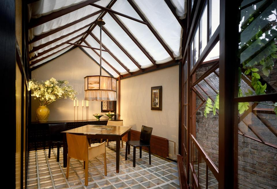 """Shadley helped to design actor Matthew Modine's Greenwich Village carriage house in 1989. """"The rectangular shapes established a Mondrian-like leitmotif we carried throughout the house, constructing a layered series of grids with wood frames and glass block to define the rooms,"""" he writes of the home. Pictured here is one of the home's dining areas."""