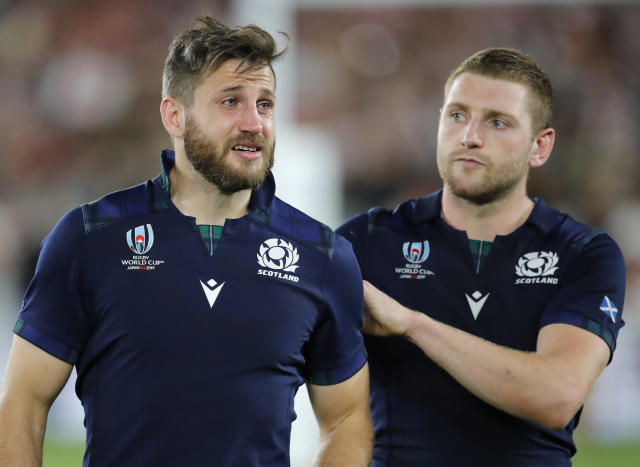 Scotland's Tommy Seymour, left, is consoled by teammate Finn Russell following their 28-21 loss to Japan in their Rugby World Cup Pool A game at International Stadium in Yokohama, Japan, Sunday, Oct. 13, 2019. (AP Photo/Christophe Ena)