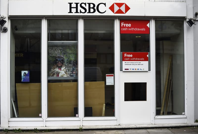 Workers carry out maintenance at a 'hole in the wall' cash dispenser at a branch of HSBC in London