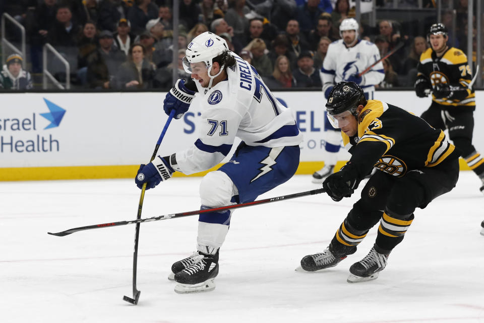 Tampa Bay Lightning's Anthony Cirelli shoots while being checked by Boston Bruins' Charlie Coyle during the third period of an NHL hockey game Saturday, March 7, 2020, in Boston. (AP Photo/Winslow Townson)